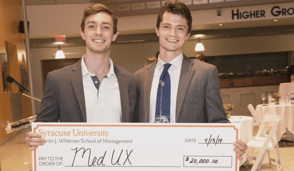 two men in suits holding a large check from Syracuse University for $20,000