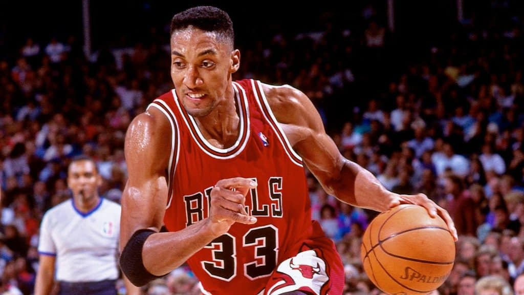 Scottie Pippen aggressively driving the ball to his left.